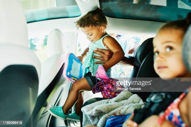 Father helping toddler daughter into car seat before beginning family trip