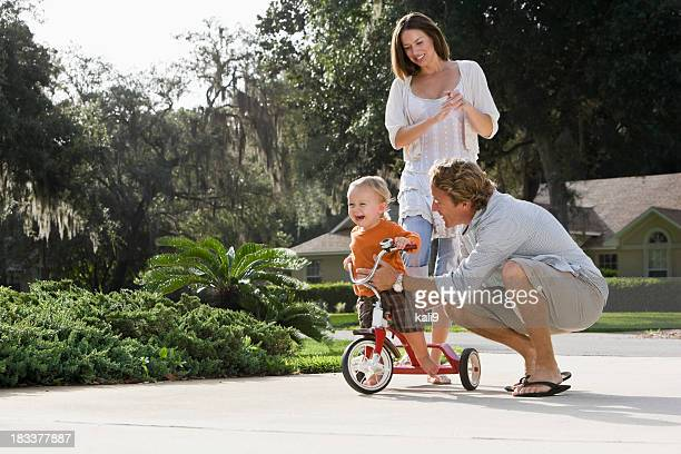 Padre ayudando a toddler ride triciclo, madre standing behind