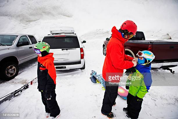 Father helping two sons prepare to go snowboarding