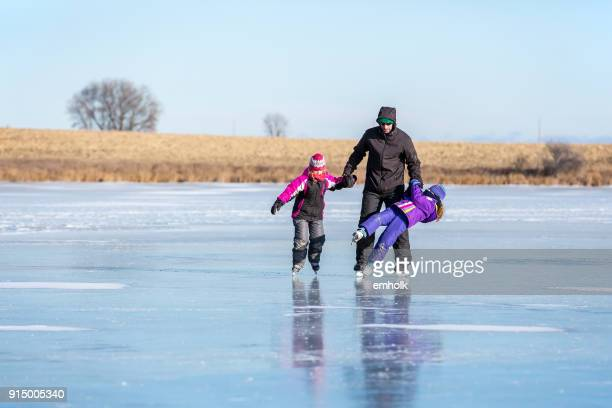father helping two young daughters ice skate - figure skating stock pictures, royalty-free photos & images