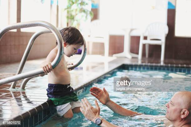 Father helping young child to get into the pool