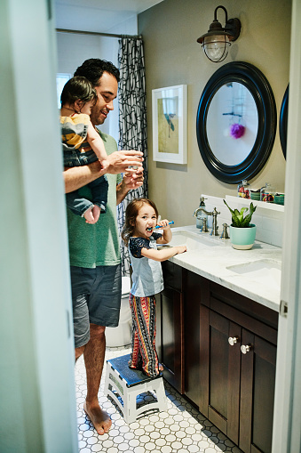 Father helping young daughter brush teeth in bathroom while holding infant son - gettyimageskorea