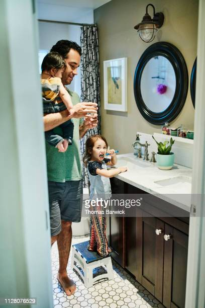 Father helping young daughter brush teeth in bathroom while holding infant son