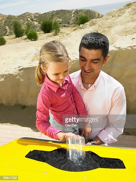 Father helping young daughter (5-7) place plastic bottle in recycling bin, Alicante, Spain,