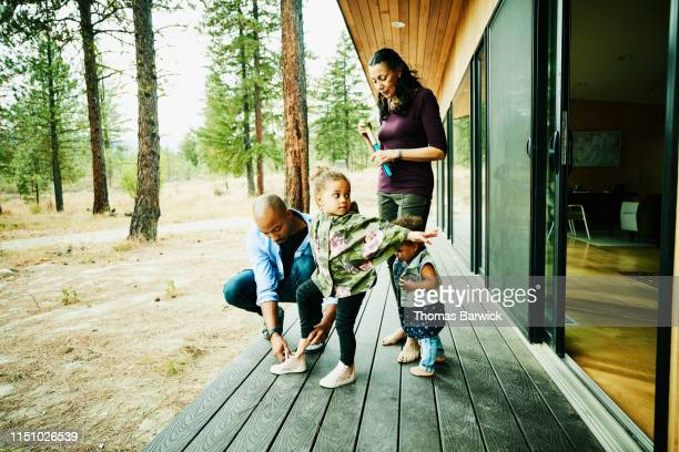 father helping young daughter put on shoes on deck of cabin before going for walk in forest - african american man helping elderly stock pictures, royalty-free photos & images
