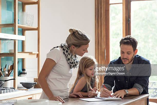 Father helping young daughter with her lessons