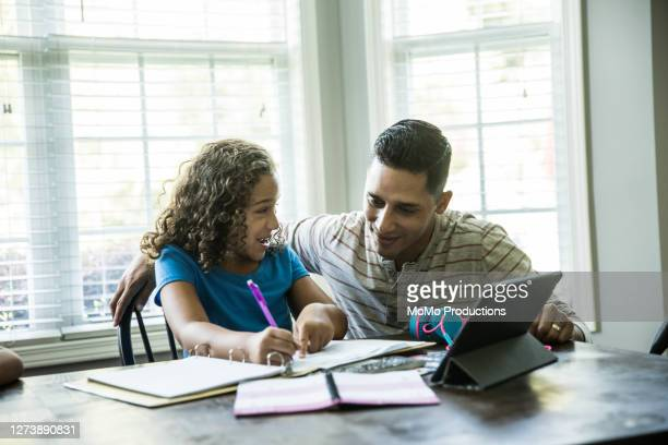 father helping young girls with schoolwork at kitchen table - homework stock pictures, royalty-free photos & images