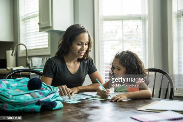 father helping young girls with schoolwork at kitchen table - ホームスクーリング ストックフォトと画像