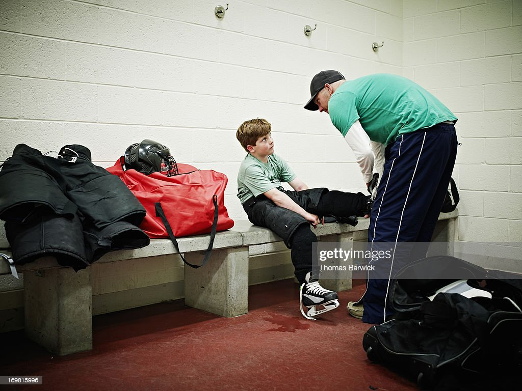Father helping young player with skates : Stock Photo