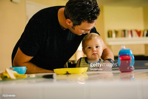 father helping young son at meal time - heshphoto stock pictures, royalty-free photos & images