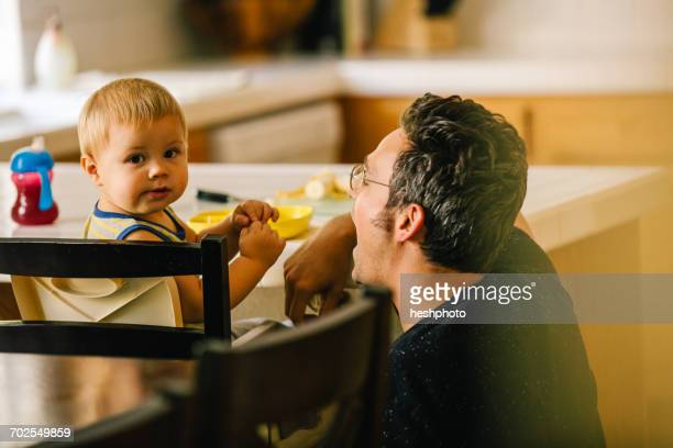 father helping young son at meal time - heshphoto fotografías e imágenes de stock
