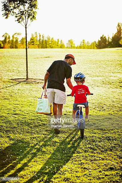Father helping young son learn how to ride bicycle