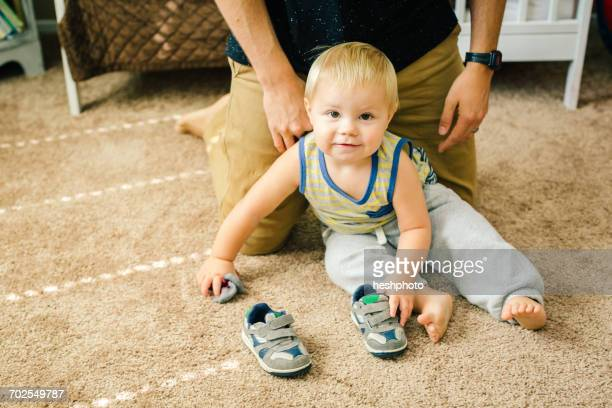 father helping young son put on shoes - heshphoto stock pictures, royalty-free photos & images