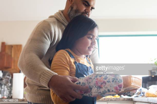 father helps daughter to take baking out of oven - genderblend stock pictures, royalty-free photos & images