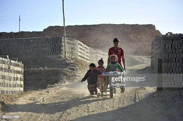 A father helps his kids to play on bricks carrying roller on the premises around the Brick Klin at Patan Nepal on Friday January 20 2017