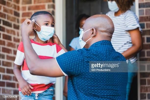 padre ayuda a su hijo a ponerse una máscara protectora para la cara - máscara protectora fotografías e imágenes de stock