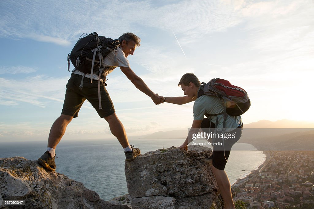 Father helps son to pinnacle summit, village below : Stock-Foto