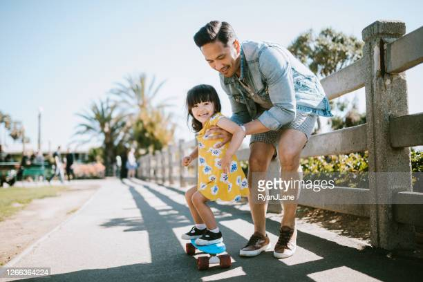 father helps young daughter ride skateboard - fun stock pictures, royalty-free photos & images