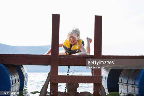 father hiding in lake from toddler daughter, silver bay, new york, usa - heshphoto photos et images de collection