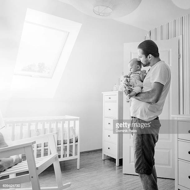Father holding and cuddling little baby boy tenderly, baby's room