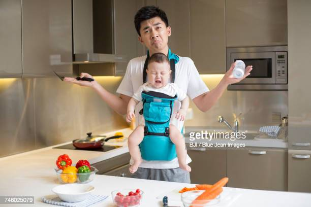 Father holding baby and cooking in the kitchen