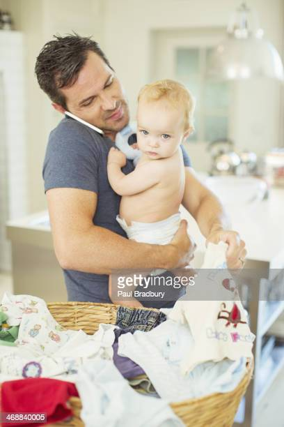 Père tenant un bébé et tout en parlant à la blanchisserie