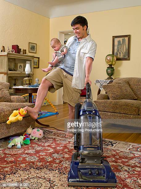 Father holding baby boy (6-11 months) and vacuuming in living room