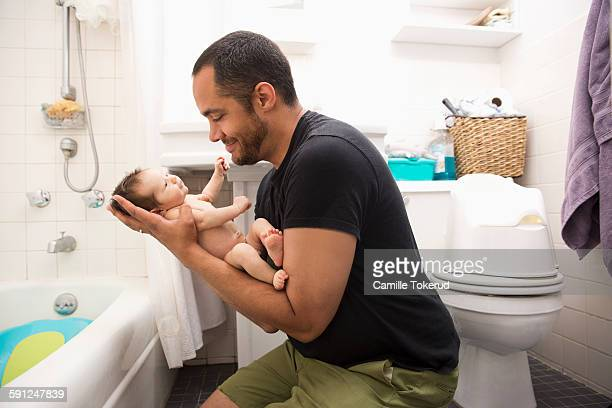 Father holding baby boy in bathroom
