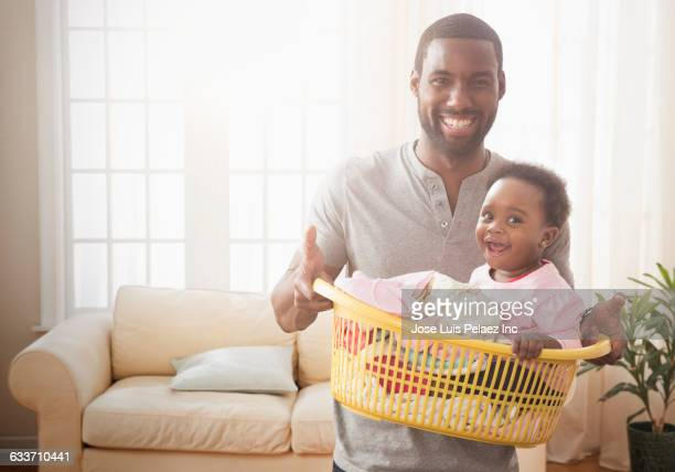 father holding baby daughter and laundry - black man holding baby stock photos and pictures