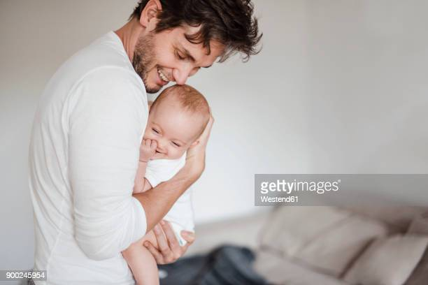 father holding baby girl at home - vater stock-fotos und bilder