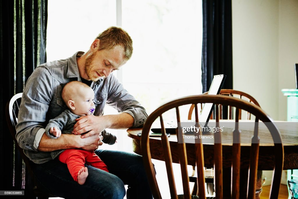 Father holding baby girl on lap at dining table : Stock Photo