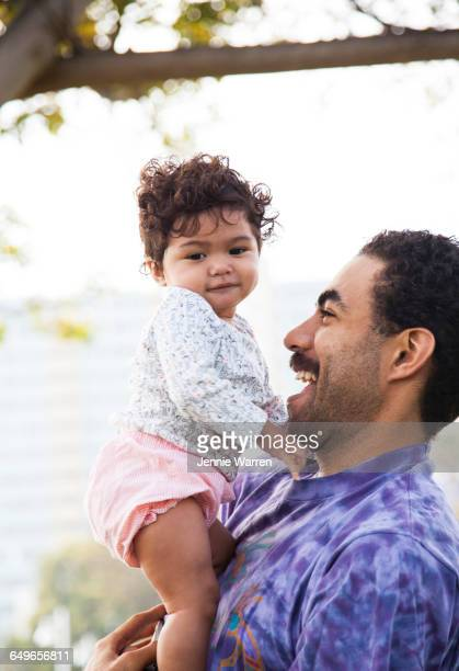 Father holding baby son outdoors