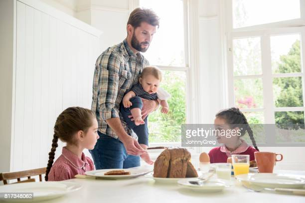 Father holding baby son serving breakfast to two daughters