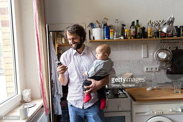 Father holding baby son while using smartphone.