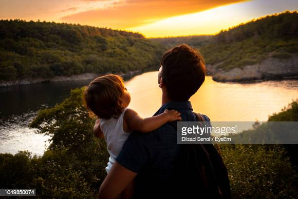 Father Holding Baby While Looking At Lake Against Sky During Sunset