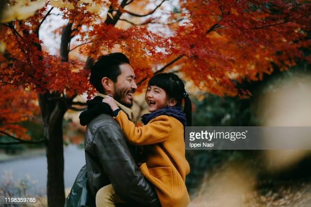 father holding cheerful little girl under autumn leaves, tokyo, japan - family stock pictures, royalty-free photos & images