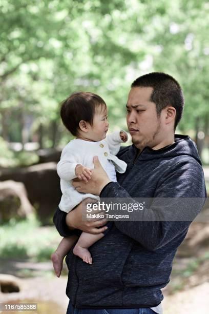 father holding child in arms - makiko tanigawa ストックフォトと画像