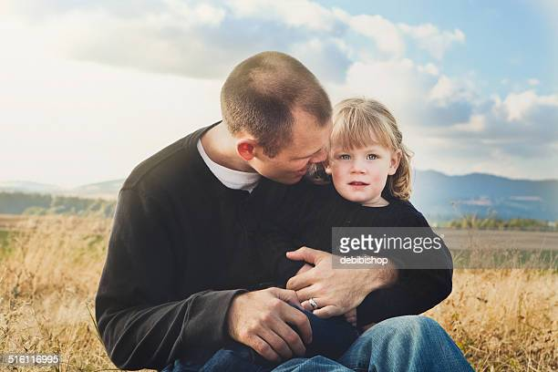 father holding & comforting daughter outdoors in nature - i love you stock pictures, royalty-free photos & images
