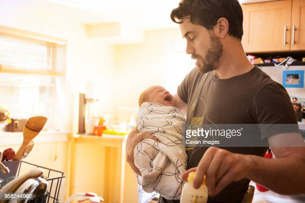 Father holding crying baby daughter in kitchen at home