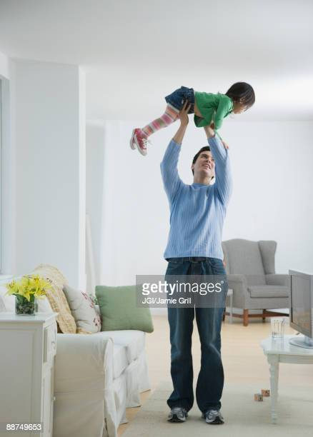 father holding daughter above head - female wrestling holds stockfoto's en -beelden