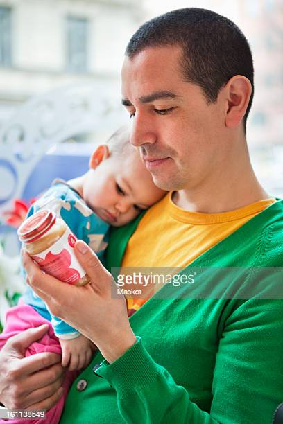 father holding daughter (0-11 months) and reading on a jar - 0 11 monate stock-fotos und bilder