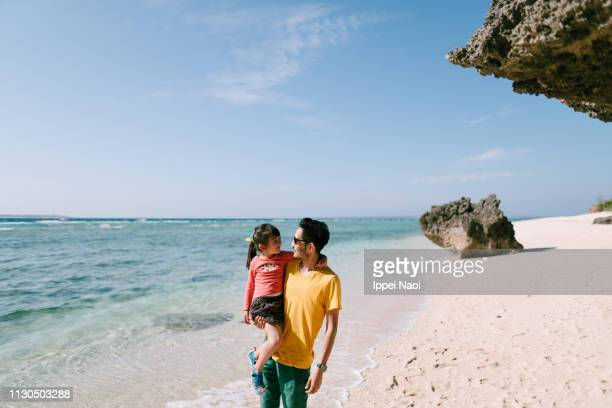 Father holding daughter and walking on tropical beach, Okinawa, Japan