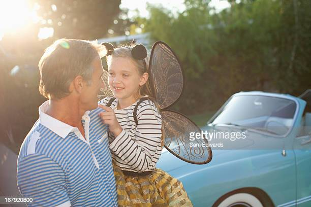 Father holding daughter in fairy wings
