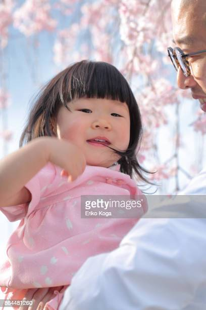Father holding daughter in his hand in front of cherry blossom