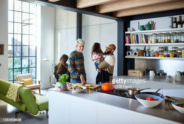 father holding daughter in kitchen with family - kitchen stock pictures, royalty-free photos & images