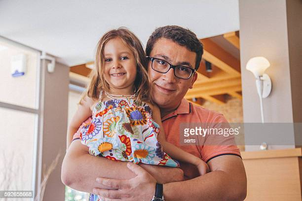 Father holding daughter posing
