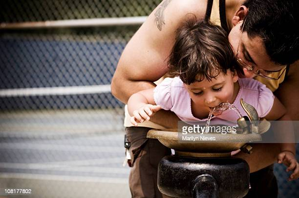 Father holding daughter up to water fountain