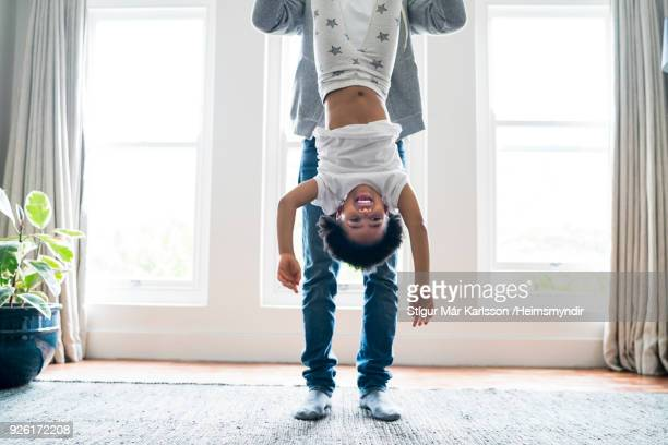 father holding daughter upside down at home - upside down stock pictures, royalty-free photos & images