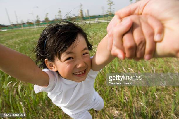 father holding daughter's (7-9) hands, spinning in circles - 揺らす ストックフォトと画像