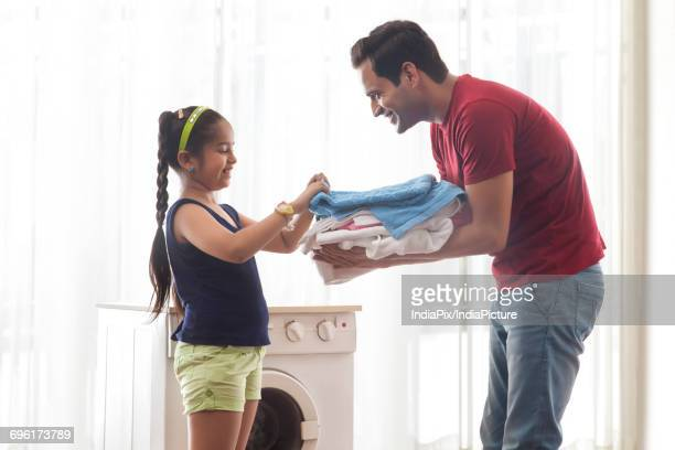 Father holding folded laundry daughter counting
